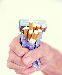 Photo of a man's hand crushing a pack of cigarettes in his fist