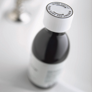 Close up image of a bottle of cough medicine.